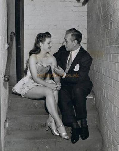 The movie star George Raft sitting with Windmill Girl Jill Anstey on the dressing room stairs at the Windmill Theatre in 1948.- Photo Courtesy Jill Millard Shapiro.