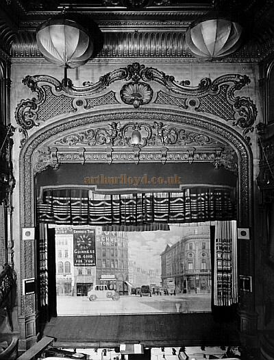 Collins' Music Hall stage and elaborate proscenium arch. The image also shows part of the orchestra pit and has a backdrop depicting Piccadilly Circus and the London Pavilion to the right. Image - Courtesy Peter Charlton.