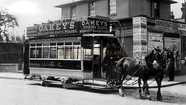Postcard showing a horse drawn omnibus on a route from the West India Docks to South Hackney, and passing a boarded up shop with fly-posters on its wall, one of which is a poster for the Hackney Empire.