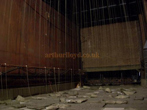 Inside the Fly Tower at the Kilburn State in a photograph taken from the Fly Floor on stage left. The roof of the temporary box which is currently filling the stage for its Bingo incarnation can be seen at the bottom of the picture, and the back of the Iron Curtain, which has been welded into place, is also visible to the left. - Photo M.L. April 2090.