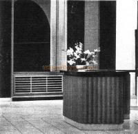 Fluted mahogany front to the reception counter and horizontal oak louvre as a radiator casing.