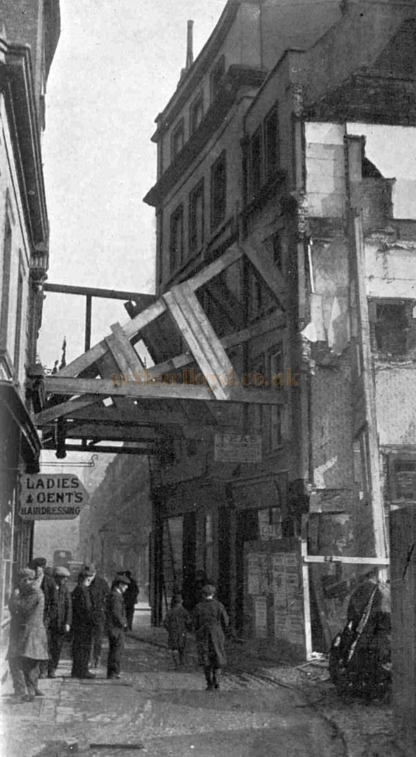 The prop of the needy: Houses in danger of collapse from the demolition of the old Oxford Theatre are stayed by timber buttresses - From The Sphere, 19th of March 1927.