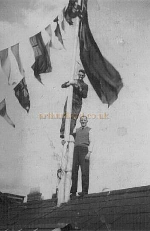 The Islington Empire is decked out with bunting and flags to celebrate the coronation of George VI in May 1937 - Courtesy Alan Towill whose father, Albert C. Towill, worked as a Maintenance Man at the Theatre at the time and is pictured up the flag pole in this photograph